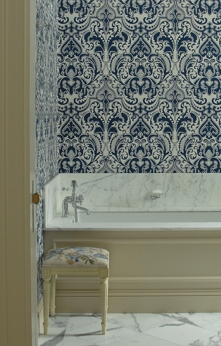 House & Home - bathrooms - damask wallpaper, blue damask wallpaper, navy damask wallpaper, white and navy wallpaper, white and navy damask wallpaper, bathroom wallpaper, wainscoted bathtub, wainscoted tub, cream wainscoted bathtub, cream wainscoted tub, drop in tub, needlepoint stool, marble floor,
