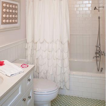 Norman Design Group - bathrooms - pink bathroom walls, pale pink walls, beadboard lower wall, beadboard half wall, bathroom beadboard, subway tiled tub surround, subway tiled bath surround, vertically stacked subway tile, vertically laid subway tile, brick laid subway tile, subway tile laid vertically, framed sea urchin, sea urchin shadowbox, scalloped shower curtain, scallop ruffled shower curtain, vintage style shower head, white sink vanity, white built in bathroom vanity, round nickel cabinet pulls, light stone counter, green hex floor tile, green floor tile, bathroom art, tub shower combo, bath shower combo, subway tile shower surround, white scalloped shower curtain, ruffled shower curtain, white ruffled shower curtain, mixed shower tiles,