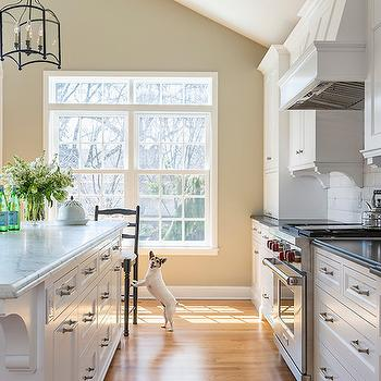 Casa Verde Design - kitchens - tan walls, arched window over french doors, arched french doors, double sash window, transom over sash window, corbel island brackets, corbel brackets, beveled subway tile, white subway tile, black counters, black countertops, inset white cabinets, inset kitchen cabinets, stainless steel range, stainless steel stove, paneled range hood, small appliance cabinet, small appliance garage, marble topped kitchen island, gray and white marble, nickel cabinet pulls, black ladder back counter stool, light hardwood floors, kitchen french doors, island corbels, kitchen island corbels, island drawers, kitchen island drawers, two tone countertops, beveled subway tile in kitchen, kitchen beveled subway tiles, vaulted ceiling, kitchen vaulted cieling,