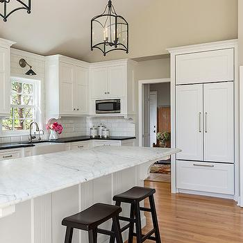 Casa Verde Design - kitchens - sloped kitchen ceiling, cabinet front white refrigerator, cabinet front french door refrigerator, overhead microwave, built in stainless steel microwave, black saddle stool, marble counter, marble island countertop, corbels, island corbels, cabinet corbels, island corbels, kitchen island corbels, white beveled subway tile, beveled subway tiled backsplash, black kitchen counters, inset cabinets, flush front cabinets, apron front sink, gooseneck faucet, sash kitchen window, kitchen window sconce, nickel wall sconce with black shade, beige walls, beige wall color, light hardwood floors, iron and glass lanterns, paneled fridge, paneled double door fridge, over the counter microwave, white marble countertop, island lanterns, kitchen island lanterns,
