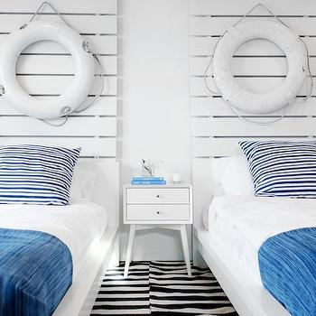 Lukas Machnik Design - boy's rooms - nautical boys room, nautical theme boys room, nautical themed boys room, plank headboards, boys room, kids headboards, white plank headboard, white and blue bedding, shared nightstand, shared boys room, shared kids room, mid century nightstand, mid century modern nightstand, striped rug, black and white striped rug, white and blue boys room, kids bedding, kids nightstands, decorative lifesavers,