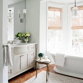Laura Casey Interiors - bathrooms - bathroom bay window, tub in bay window, bath in bay window, freestanding tub, pedestal tub, roll top pedestal tub, floor mount tub faucet, light woven shades, woven roman shades, bathroom hardwood floors, gray scroll print rug, gray and ivory rug, bathroom area rug, antiqued gold accent table, bathroom accent table, gray built in vanity, gray bathroom vanity, vanity alcove, bow front vanity, brushed nickel cabinet pulls, marble counter, marble vanity counter, vanity length mirror, wall length vanity mirror, mirror mounted wall sconce, mirror inset wall sconce, sconces over mirror, light gray walls, bay window bathroom, bathtub bay window, bay window tub, bay window bathtub, tub in bay window, bathtub in bay window, elegant bathrooms, gray washstand, curved sink vanity, curved sink washstand, mercury glass bell pendant, lighting over bathtub,