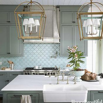 House Beautiful - kitchens - Sherwin Williams - Retreat - green cabinets, green kitchen cabinets, white marble countertops, brass lanterns, brass kitchen lanterns, island lanterns, brass island lanterns, brass kitchen island lanterns, twin sinks, farmhouse sinks, whitehouse sinks, fireclay sinks, face to face sinks, sinks facing each other, kitchen sinks facing each other, island with 2 sinks, kitchen island with 2 sinks, large kitchen island, green kitchen island, green kitchens, cottage kitchen, green cottage kitchens, double kitchen sink, double farmhouse sinks, robins egg blue, robin eggs blue tiles, fan tiles, terracotta tiles, blue terracotta tiles, robins egg blue terracotta tiles, fish scale tiles, blue fish scale tiles, robins egg blue backsplash, blue fan tiles, fan tile backsplash, blue fan tile backsplash, robins egg blue backsplash, swing arm pot filler, french kitchen hood, studded kitchen hood,