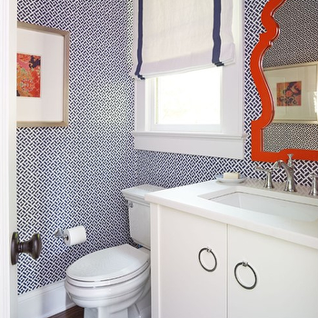 Laura Casey Interiors - bathrooms - orange lacquered mirror, modern orange mirror, orange queen anne mirror, contemporary white vanity, nickel ring pull hardware, white counter, rectangular porcelain sink, chrome faucet, navy geometric wallpaper, navy fretwork wallpaper, wallpapered powder room, orange abstract art print, blue and green striped rug, window trim, navy grosgrain trimmed roman shade, navy and white roman shade, navy and white wallpaper, modern queen anne mirror, powder room wallpaper, orange mirror, orange vanity mirror, orange lacquer mirror, navy wallpaper, powder room wallpaper, white and navy roman shade, blue and orange powder room, navy and orange powder room,