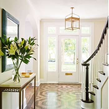 Laura Casey Interiors - entrances/foyers - light tan walls, glass sidelights, front door sidelights, front door transom window, transom window over front door, glass front door, white front door, black handrail, glossy black handrail, white spindles, turned white spindles, geometric stained hardwood floors, patterned stained hardwood floors, octagon stained hardwood floors, entryway floor ideas, foyer floor ideas, greek key console table, gold greek key console table, greek key console table with stone top, black mirror, arched doorway, brass lantern pendant, arch top lantern pendant, arch top brass lantern, foyer lantern, lantern pendant over front door, foyer lighting, foyer lighting ideas, door sidelights, octagon wood floors, octagonal wood floor, greek key foyer table, brass foyer table, brass greek key table,