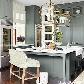 House Beautiful - kitchens - Sherwin Williams - Retreat - green cabinets, green kitchen cabinets, double fridges, twin fridges, glass door fridge, glass front fridge, sub zero, sub zero fridge, kitchen pass through, white marble countertops, brass lanterns, brass kitchen lanterns, island lanterns, brass island lanterns, brass kitchen island lanterns, twin sinks, farmhouse sinks, whitehouse sinks, fireclay sinks, face to face sinks, sinks facing each other, kitchen sinks facing each other, island with 2 sinks, kitchen island with 2 sinks, large kitchen island, green kitchen island, kitchen island legs, pull out microwave, island microwave, kitchen island bench, island bench, slipcovered island bench, floor to ceiling cabinets, floor to ceiling kitchen cabinets, green pantry cabinets, mirrored pantry doors, green kitchens, cottage kitchen, green cottage kitchens,