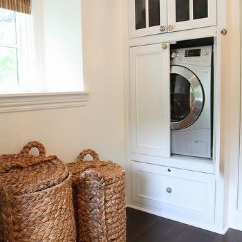 M. E. Beck Design - closets - seagrass laundry hamper, woven laundry hamper, woven laundry hamper with lid, dark hardwood floors, deep window ledge, striped brown roman shade, washer dryer combo, combination washer dryer, all in one washer dryer, closet washer dryer, washer dryer in closet, hidden washer dryer, washer dryer cabinet, white built in cabinet, mercury glass cabinet pulls, mercury glass knobs, glass front cabinets, closet washer and dryer, washer dryer in closet, hidden washer and dryer, concealed washer dryer, concealed washer and dryer,