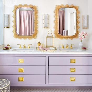 Style at Home - bathrooms: calacatta and thassos tiles, herringbone floor, herringbone tiled floor, marble herringbone tiled floor, calacatta herringbone tiles, thassos herringbone tiles, herringbone bathroom floor, lavender washstand, lavender vanity, lavender sink vanity, calacatta countertops, calacatta marble countertops, gold shower kit, gold faucet, lavender double vanity, his and her sinks, resin mirror, vintage resin mirror, vintage mirrors, crystal and brass sconces, scalloped mirrors, brass vanity hardware, brass lantern, gold lantern,