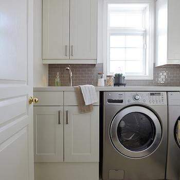 Nest Design Studio - laundry/mud rooms - white and gray laundry room, laundry room, mini subway tiles, gray mini subway tiles, mini gray subway tiles, laundry room backsplash, laundry room cabinets, off white ocuntertops, silver washer dryer, laundry room sink,