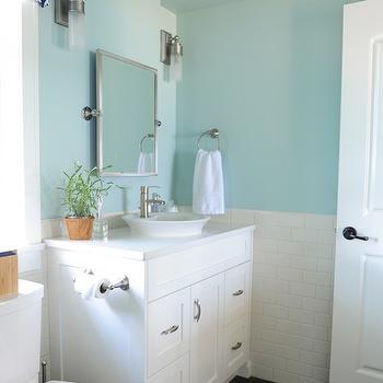 Maria Killam Interior Design - bathrooms - Benjamin Moore - Palladian Blue - white and blue bathrooms, palladian blue, blue wall paint, blue paint colors, blue bathroom paint, blue bathroom paint colors, half painted bathroom walls, half tiled walls, half tiled subway tiles, white glass and nickel sconces, rectangular pivot mirror, round sink, bowl sink, shallow bowl sink, bathroom valance, navy geometric valance, white and navy valance, toilet under window, white washstand, satin nickel faucet,
