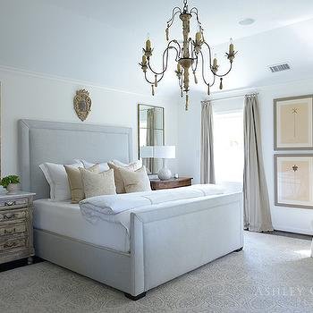 Ashley Goforth Design - bedrooms - pressed botanical prints, botanical prints, botanical art, art between windows, linen drapes, linen curtains, vaulted tray ceiling, dark hardwood floors, neutral print rug, neutral medallion rug, medallion print rug, gray bed, gray upholstered bed, white bed linens, beige hotel bedding, beige pillows, patterned beige pillow, distressed nightstand, french nightstand, wooden nightstand, taupe table lamp, ceramic taupe table lamp, art over headboard, mirrors over nightstand, mirror over nightstand, gilt mirror, french chandelier, iron and carved wood chandelier, french style chandelier, white rolled armchair, white armchair, gold quatrefoil floor lamp, gilt quatrefoil floor lamp, bedroom chandeliers, mismatched nightstands, mismatched bedside tables, beige curtains, light grey bed, mirrors over nightstands, mirrors behind nightstands, white and beige sheet set, mismatched nightstands, gray lamps, candle chandelier, modern french bedrooms,