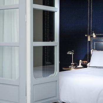 Only You Hotel - bedrooms - bifold bedroom door, gray bifold door, glass paned bifold door, navy hotel bedding, navy hotel pillow, navy blue upholstered headboard wall, upholstered headboard wall, nailhead wall trim, navy blue headboard, navy headboard with nailhead trim, swing arm wall lamp, headboard wall lamp, nickel apothecary lamp, apothecary table lamp, silver side table, white sheets, white bed linens, navy blue bedroom, navy and white bedding, headboard accent wall, headboard accent wall ideas, headboard focal wall ideas, white and navy shams, accent wall, bedroom accent wall, accent wall bedroom, navy upholstered wall, navy wall, navy fabric wall, nailhead wall, nailhead accent wall, navy headboard, navy studded headboard, brass swing arm sconces, navy bedrooms,