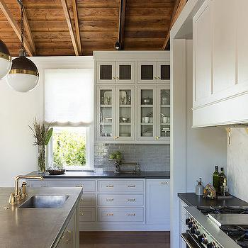 Beautiful kitchen features truss ceiling accented with hicks pendants