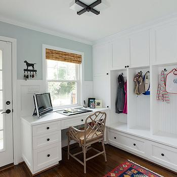 Urban Building Group - laundry/mud rooms - combination mud room, combination mudroom office, office in mudroom, desk in mud room, built in desk, workstation in mud room, built in desk, built in mud room lockers, mud room cabinetry, mud room cabinets, wall to wall mudroom storage, floor to ceiling mud room storage, beadboard paneled mud room lockers, oil rubbed bronze cabinet pulls, built in mudroom bench, mud room storage bench, single french patio door, desk under window, blue walls, bamboo shade, bamboo window shade, square flushmount pendant, faux bamboo armchair, chippendale armchair, chinoiserie arm chair, mudroom desk, mudroom workstation, open mudroom lockers,