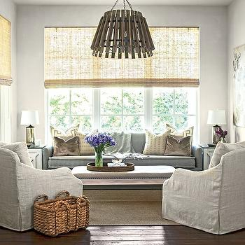 Southern Living - living rooms - tall sash windows, light woven shades, woven window shades, matchstick bamboo shade, gray blue sofa, taupe velvet pillow, ivory pillow, greek key pillow, mercury glass lamp, white end table, slipcovered linen armchair, linen armchair, seagrass basket, seagrass basket with handles, ottoman coffee table, woven tray, upholstered ottoman coffee table, sisal rug, natural fiber rug, dark hardwood floors, wooden slat pendant, slatted wooden pendant, sofa with 1 cushion, 1 cushion sofa, gray 1 cushion sofa, sofa in front of window, bench coffee table, living room nook,