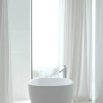 Deborah Oppenheimer Interior Design - bathrooms - sleek bathrooms, modern bathrooms, sleek white bathrooms, modern white bathrooms, minimalist bathrooms, egg shape tub, egg shaped bathtub, floor mounted tub filler, floor to ceiling windows, floor to ceiling bathroom windows, white curtains, white drapes,