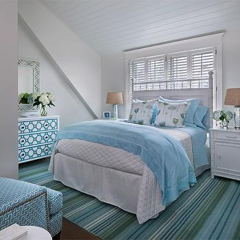 Cottage Company Interiors - bedrooms - cottage bedrooms, white and blue bedrooms, white and blue cottage bedroom, bed in front of window, headboard in front of window, plantation shutters, bedroom plantation shutters, white bamboo headboard, faux bamboo headboard, white and blue bedding, white nightstands, bamboo nightstands, white bamboo nightstands, faux bamboo nightstands, mercury glass lamps, striped rug, blue and green rug, blue and green striped rug, attic bedrooms, sloped ceiling, sloped bedroom ceiling, white lattice mirror, bungalow 5 mirror, geometric chest, geometric dresser, geometric overlays, drawer overlays, geometric drawer overlays, 3 drawer chest, 3 drawer dresser, blue geometric chair, blue wingback chair,