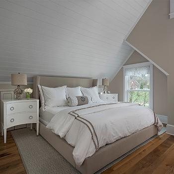 Cottage Company Interiors - bedrooms - Benjamin Moore - Baby Fawn - beige bedrooms, white and beige bedrooms, attic bedrooms, attic bedroom ideas, sloped ceiling, sloped bedroom ceiling, planked ceiling, sloped plank ceiling, beige bed, wingback bed, beige wingback bed, kids bed, king beige bed, white and beige bedding, monogram bolster pillows, beige walls paint, beige paint colors, gray diamond rug, diamond pattern rug, gray diamond print rug, white nightstands, 2 drawer nightstands, curved nightstands, white curved nightstands, built in closets, attic closets, beige wingback headboard, rug under bed, beige and gray bedrooms,