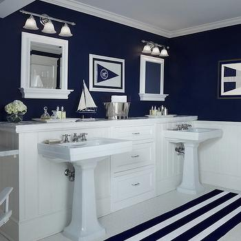 Cottage Company Interiors - bathrooms - nautical bathrooms, nautical kids bathrooms, kids bathrooms, kids bathroom ideas, boys bathrooms, boys bathroom ideas, navy walls, navy bathroom walls, navy upper walls, navy blue upper walls, vertical paneling, bathroom paneling, paneled bathrooms, tongue and groove, mirror with shelf, white mirror with shelf, bell jar sconce, triple bell jar sconce, white glass bell jar sconce, bathroom sconces, kids bath lighting, kids bathroom lighting, pedestals inks, shared kids bathroom, shared boys bathrooms, built in cabinets, built in bathroom cabinets, navy striped rug, navy bath mat, floating vanity, floating marble vanity, directors chair, navy directors chair,