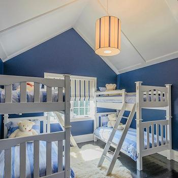 Sotheby's Realty - boy's rooms - sheepskin rug, flokati rug, espresso hardwood floors, bunk room, bunk room ideas, boys bunkroom ideas, vaulted ceilings, batten trimmed vaulted ceiling, red car art, kids car art, navy blue walls, navy wall color, dark blue walls, navy blue bunk room, blue bunk room ideas, tube shaped drum pendant, elongated drum pendant, blue striped bedding, tonal blue striped duvet, stripey blue bedding, blue and white striped window shade, blue striped roman shade, kids bedding, vertical striped duvet, vertical striped bedding, 2 sets of bunk beds, 4 beds, board and batten ceiling, white and blue boys room, white and blue kids room,