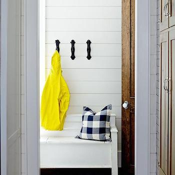Style at Home - laundry/mud rooms - tongue and groove, tongue and groove walls, painted tongue and groove walls, horizontal wood planked wall, horizontal wood paneling, white storage bench, white bench, white mud room bench, mud room storage, mud room seating, iron wall hooks, black wall hooks, navy checkered pillow, navy buffalo check pillow, braided sisal rug, natural fiber rug, hardwood floors, cottage mud room, country mud room, mud room wall treatments, mud room wall hooks, mudroom bench, freestanding mudroom bench,