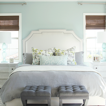 Shea McGee Design - bedrooms - blue walls, blue bedroom walls, nightstand in front of window, bed in between windows, white headboard, white headboard with nickel nailhead, gray bed linens, gray bedding, white bed linens, gray and yellow floral pillow, gray and yellow floral sham, aqua blue lumbar pillow, blue paisley lumbar pillow, gray velvet upholstered stool, gray tufted x stool, tufted velvet x stool, seating at foot of bed, seating at end of bed, bedroom seating ideas, white three drawer nightstand, traditional white nightstand, blue glass table lamp, aqua blue table lamp, frosted blue table lamp, gray chevron rug, rug on carpet, rug layered on carpet, rug on top of carpet, moroccan print drapes, white and gray moroccan drapes, moroccan print curtains, dark woven shades, woven window shades, beige carpet, wall to wall carpeting, studded headboard, nailhead headboard, aqua table lamps, gray x stools, bedroom stools,
