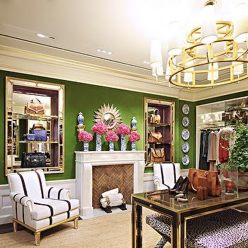 closets - tory burch closet, moss green walls, green walls, green wall color, wainscoting, closet wainscoting, traditional fireplace, closet with fireplace, brick herringbone firebox, closet chandelier, black and brass table, black table with brass trim, black and white leopard print stool, black and white striped chair, blue and white vase, gold sunburst mirror, mirror over fireplace, recessed mirrored shelves, mirrored shelving, gold mirrored shelves, built in mirrored shelves, purse shelves, purse display, purse cubbies, braided sisal rug, walk in closet seating, closet seating, deep crown molding, gold trimmed crown molding, decorative wall plates, round gold chandelier, modern round gold chandelier, tiered gold chandelier, mirror backed shelves, mirror lined shelves, wainscoting in closet, herringbone firebox, tiered brass chandelier, tiered chandelier, black and gold table, black and gold console table, black and brass console table, x stools, black and white x stools, mirrored shelves, built in mirrored shelves, inset mirrored shelves, black and white chairs, striped chairs,