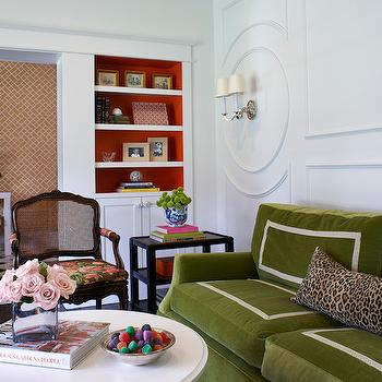 Wolfe Design House - living rooms - green velvet sofa, velvet sofa with grosgrain trim, moss green velvet sofa, sofa with grosgrain trim, leopard print pillow, leopard lumbar pillow, decorative wall trim, decorative molding, decorative wall molding, black end table with shelves, round white coffee table, art books, cane back chair, floral cane back arm chair, orange backed shelves, orange backed built ins, built in shelves, built in shelves over cabinet, two arm nickel sconce, two arm sconce with shade, black and white chevron floors, black and white chevron floor tile, white parsons console table, modern white console table, x stool, orange chinoiserie wallpaper, geometric orange wallpaper, foyer wallpaper, hallway wallpaper, white mirror, white chinoiserie mirror, stacked art books, eclectic living room, chinoiserie lattice wallpaper, border sofa, green couch, moss green sofa, circular wall moldings, circular wall trim, tiered end tables, black tiered end table, round coffee tables, black cane chair, painted backs of shelves,