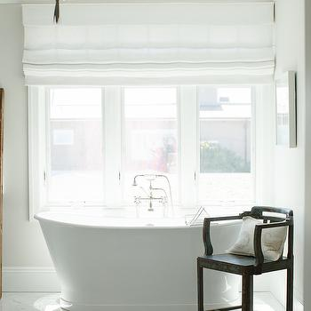 Owens and Davis - bathrooms - freestanding tub, bathtub below window, white linen roman shade, white roman shade, vintage tub filler, vintage style tub filler, distressed chair, bathroom chair,