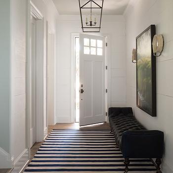 Reu Architects - entrances/foyers - Benjamin Moore - Decorators White - foyer, foyer ideas, foyer lanterns, black and white rug, striped rug, black and white striped rug, foyer rugs, foyer bench, blakc bench, black tufted bench, black velvet bench, tufted bench, velvet bench, bench on caster legs, caster legs on bench, round sconces, paneled front door, decorators white, planked walls, foyer planked walls, planked foyer walls,