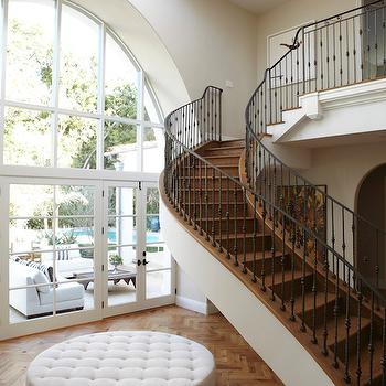 OXA Architecture - entrances/foyers: floating staircase, winding staircase, winding floating staircase, 2 story foyer, two story foyer, iron spindles, iron banister, foyer, foyer ideas, 2 story foyer ideas, herringbone floor, wood herringbone floor, foyer ottoman, round ottoman, oversized ottoman, ivory tufted ottoman, round ivory ottoman, arched windows,