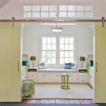 Jennifer Palumbo - boy's rooms: green barn doors, sliding barn doors, kids room barn doors, sliding kids barn doors, blue and green kids room, shared kids room, shared boys room, nautical kids room ideas, nautical boys room ideas, beadboard clad walls, beadboard paneled walls, white beadboard walls, beadboard vaulted ceilings, transom window, interior transom window, vaulted ceiling transom window, green rug, built in bed, built in storage bed, beadboard paneled bed, built in storage window seat, beadboard window seat, brushed nickel cup pulls, built in nightstand, double sash window, industrial nickel pendant light, nickel yoke pendant, modern green stool, lime green stool, green bedding, navy blue pillow, chevron seat cushion, chevron window seat cushion, blue fish pillow, green laundry hamper, green canvas hamper, taboret stool, green taboret stool, interior barn doors, kids barn doors, built in beds, built in kids beds, beadboard beds, kids beadboard beds, built in beadboard bed, kids window seats,