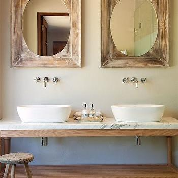 bathrooms - distressed mirror, distressed vanity mirror, his and her sinks, oval sinks, vessel sinks, oval vessel sinks, wall mounted faucets, wood washstand, white marble countertops, rustic stool, jute rug,
