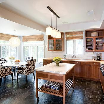 Ashley Goforth Design - kitchens - tray ceiling, kitchen tray ceiling, tray ceiling in kitchen, island lighting, kitchen island lighting, freestanding kitchen island, freestanding center island, kitchen island on wheels, island on wheels, white marble countertop, chestnut colored cabinets, chestnut kitchen cabinets, gray brick tiled floors, perimeter countertops, butcher block, butcher block countertops, glass front kitchen cabinets, stainless steel kitchen hood, integrated gas stove, eat in kitchen, eat in kitchen ideas, white capiz pendant, capiz chandelier, oval dining table, saarinen oval table, saarinen oval dining table, black and white dining chairs, kitchen tv,