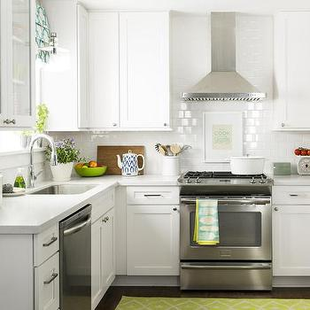 HGTV - kitchens - kitchen accents, kitchen accessories, styled kitchen, white shaker cabinets, creamy white cabinets, light gray countertops, white gray counters, white gray countertops, light gray quartz countertops, white gray quartz, white gray quartz countertops, kitchen subway tiles, kitchen with subway tiles, stainless steel kitchen hood, stainless steel stove, double door fridge, fridge with freezer drawer, green kitchen rug, art behind stove, stove art, kitchen art, kitchen art ideas,