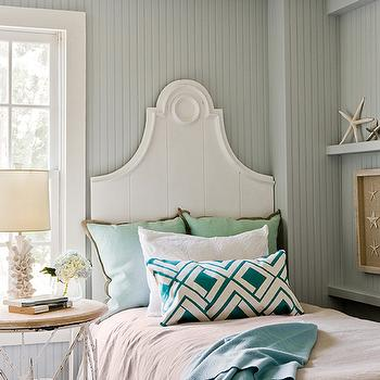 Jennifer Palumbo - bedrooms: white barnacle lamp, barnacle lamp, white arched headboard, arched wooden headboard, beach bedroom, beachy bedrooms, beadboard paneling, beadboard clad walls, beadboard bedroom walls, gray green beadboard, painted beadboard paneling, mint green pillow, jute trimmed pillow, beige bedding, beige bed sheets, emerald green lumbar pillow, green and white lumbar pillow, emerald green geometric pillow, blue green throw, distressed white iron nightstand, shabby chic nightstand, white iron side table, floating wall ledge, starfish, starfish shadowbox, barnacle table lamp, gray beadboard, cottage bedrooms,