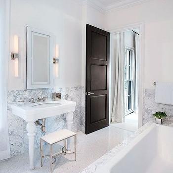 Luxe Interiors and Design - bathrooms - black bathroom door, black interior door, speckled gray floors, speckled gray and white floors, speckled bathroom floors, drop in tub, drop in bath, marble tub surround, carrera marble tub surround, marble tiled bath surround, chrome vanity stool, chrome bathroom stool, chrome and leather vanity stool, two legged sink, two leg sink, 2 legged sink, 2 leg sink, two leg porcelain sink, mirrored medicine cabinet, mirror front medicine cabinet, tubular wall sconce, frosted glass bathroom sconce, tubular frosted glass wall sconce, marble tiled half wall, marble tiled bathroom wall, carrera marble tile, carrera marble, gray and white marble tile, marble wainscoting, marble bathroom wainscoting, parisian sink, parisian pedestal sink,