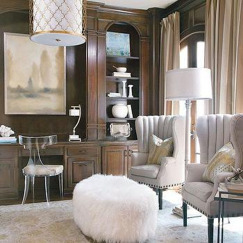 Luxe Interiors and Design - dens/libraries/offices - mongolian wool ottoman, fluffy white ottoman, channel back linen chair, channel back linen wingchair, channel tufted wingchair, wooden floor lamp, persian rug, neutral persian rug, lucite chair, lucite klismos chair, dark stained wall paneling, stained wall paneling, built in desk, built in bookcase, arched built in bookcase, dark stained built ins, home office built ins, arched window, monochromatic landscape, abstract landscape painting, dark hardwood floors, gold quatrefoil drum pendant, gold quatrefoil pendant light, arched built ins, beige and ivory striped drapes, vertically striped drapes, oval ottoman, oval sheepskin ottoman, lucite desk chair, ivory and gold rug, gold trellis pendant,