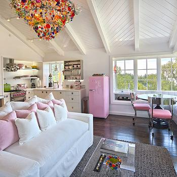 Jessica Risko Smith Interior Design - living rooms - one room apartment, one room apartment ideas, one room living spaces, vaulted tongue and groove ceilings, herringbone tongue and groove ceilings, multi colored chandelier, colorful chandelier, jute rug, braided jute rug, built in bookcase, built in white bookcase, acrylic coffee table, see through coffee table, pink pillows, stainless steel console table, L shaped kitchen, compact kitchen, small apartment kitchen, flush front cabinets, inset cabinet hardware, inset nickel cabinet pulls, stainless steel floating shelves, stainless steel kitchen shelves, gas stove, stove with pink knobs, compact kitchen ideas, compact living spaces, pink smeg fridge, smeg refrigerator, retro pink fridge, window seat banquette, tufted window seat banquette, white tufted window seat, corner window seat, L shaped window seat, pedestal dining table, black pedestal table, silver klismos chair, aluminum klismos chair, klismos chair, studio apt, studio apartment, studio apartment ideas, herringbone ceiling, herringbone paneled ceiling, built in platerack, pink fridge, pink refrigerator, vintage pink fridge, convertible sofa, slipcovered convertible sofa,