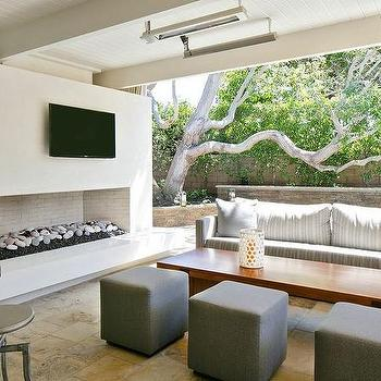 Kelly Nutt Design - decks/patios - outdoor fireplace, modern outdoor fireplace, fireplace with river rocks, outdoor tv, outdoor lounge, outdoor sofa, gray striped sofa, gray cube stools, gray cube ottomans, teak coffee table, covered patio with fireplace, covered deck with fireplace, beadboard patio ceiling, beadboard deck ceiling,
