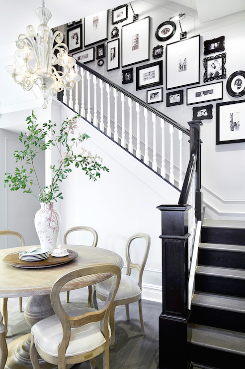 Rob Stuart Interiors - dining rooms - black and white staircase, black and white stairwell, white spindles, black banister, black staircase banister, staircase photo wall, stairwell photo wall, black and white photo wall, staircase gallery, eat in kitchens, round dining table, light wood dining table, light wood dining chairs,