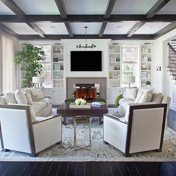 RT Abbott Construction - living rooms - coffered ceiling, dark coffered ceiling, dark brown coffered ceiling, espresso coffered ceiling, living room coffered ceiling, coffered ceiling in living room, gray fireplace surround, gray fireplace tiles, mirrored fireplace surround, living room built ins, living room built in bookcase, living room built in bookshelf, built in bookcases, built in bookshelf, living room bookcase, living room bookshelf, iron and wood coffee tables, sofas facing each other, face to face sofas, linen sofas, gray ikat rug, white and gray ikat rug, wood framed chairs,