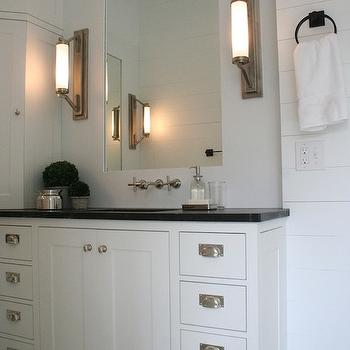 Enjoy Company - bathrooms - corner vanity cabinet, corner cabinet, built in corner cabinet, corner bathroom cabinet, white cabinets, white footed bathroom vanity, bathroom vanity with feet, nickel bin pull hardware, black counters, black vanity counters, shiplap in bathroom, shiplap backsplash, white wood paneled backsplash, wall mount faucet, wall mount hot and cold faucet, inset vanity mirror, corner countertop cabinet, white vanity cabinets, white bathroom cabinets, bathroom wall lights, vanity wall lights,