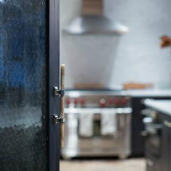 Jenny Wolf Interiors - kitchens - black door, black kitchen doors, chicken wire door, wood herringbone floor, stainless steel kitchen hood, wolf range, wolf stove,