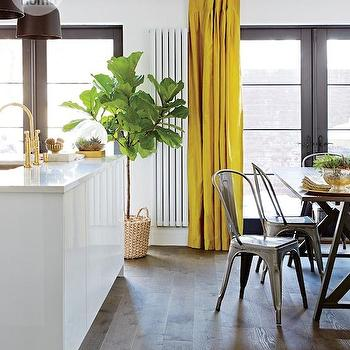 Style at Home - kitchens - tolix chairs, steel dining chair, metal dining chair, trestle dining table, wide plank hardwood floors, yellow drapes, bright yellow drapes, acid yellow drapes, glossy white cabinets, modern white kitchen island, white quartz counters, white quartz countertops, undermount kitchen sink, kitchen island with sink, brass gooseneck faucet, brass bridge faucet, fiddle leaf fig, black patio doors, black framed patio doors, hi gloss kitchen cabinets, hi gloss white cabinets, yellow silk drapes, yoke pendant, steel yoke pendant, gray and yellow kitchen, gray and yellow kitchen ideas, tolix dining chairs, yellow curtains,