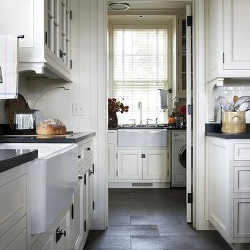 Miles Redd - kitchens: door with transom window, transom window over door, dark gray flagstone floors, gray flagstone floors, flagstone floors, country kitchen ideas, farmhouse kitchen ideas, butlers pantry off kitchen, farmhouse kitchen, two farmhouse sinks, farm sink, two sinks, black counters, ivory cabinets, ivory shaker cabinets, inset shaker cabinets, exposed cabinet hardware, oil rubbed bronze latch hardware, latch pull hardware, upper cabinet corbels, corbel cabinet brackets, glass front cabinets, beadboard walls, subway tile, subway tile backsplash, ivory kitchen ideas, laundry room off kitchen, mudroom transom window, flagstone, flagstone floor, kitchen flagstone floor, kitchen flagstone tiles, mudroom off kitchen, mudroom off of kitchen, laundry room off kitchen,