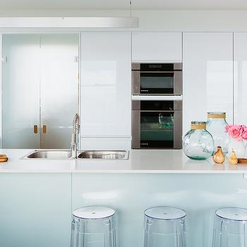 The Home Australia - kitchens - aqua blue and white kitchen, ghost stools, backless acrylic stool, backless acrylic counter stool, white waterfall edge counter, white kitchen counters, waterfall edge island counter, waterfall edge peninsula island counter, dual basin stainless steel sink, dual basin sink, peninsula sink, spray faucet, spray gooseneck faucet, stainless steel wall oven, single wall oven, stainless steel microwave, integrated microwave, microwave over wall oven, glossy white kitchen cabinets, white lacquered cabinets, lacquered kitchen cabinets, frosted glass pantry doors, blue glass pantry doors, built in wine cubbies, built in wine storage, open shelving, modern linear pendant, linear pendant light, frosted glass pantry doors, bi fold pantry doors, glass bi fold pantry doors, frosted glass bi fold pantry doors, over the counter wine rack, built in wine rack, acrylic backless barstools, white lacquer kitchen cabinets,