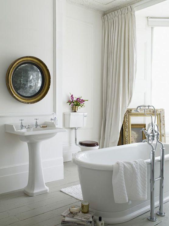 bathrooms - freestanding tub, freestanding bath, bath in center of room, bath in middle of room, floor mount faucet, floor mount tub faucet, faucet with hand shower, wainscoting in bathroom, bathroom wainscoting, antiqued convex mirror, bathroom convex mirror, convex vanity mirror, round convex mirror, gray floors, painted gray floors, painted hardwood floors, bathroom bay window, ivory drapes, ivory floor length drapes, gray plank floor,