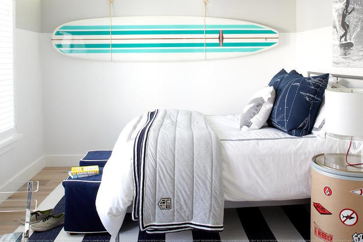 White Lined With A White And Aqua Stripe Surfboard Suspended From The