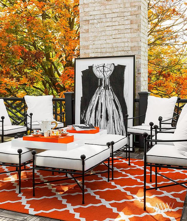 Orange And Black Patio Features Wrought Iron Chairs Surrounding Ottomans Covered In White Cushions With Piping Atop An Trellis